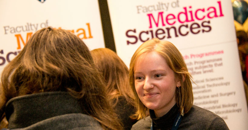 Student discussing medicine applications at an open day.