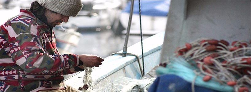 Many of our publications look at the implications of fishing policies for those working in rural fishing communities. Pictured is a fisherman untangling nets.