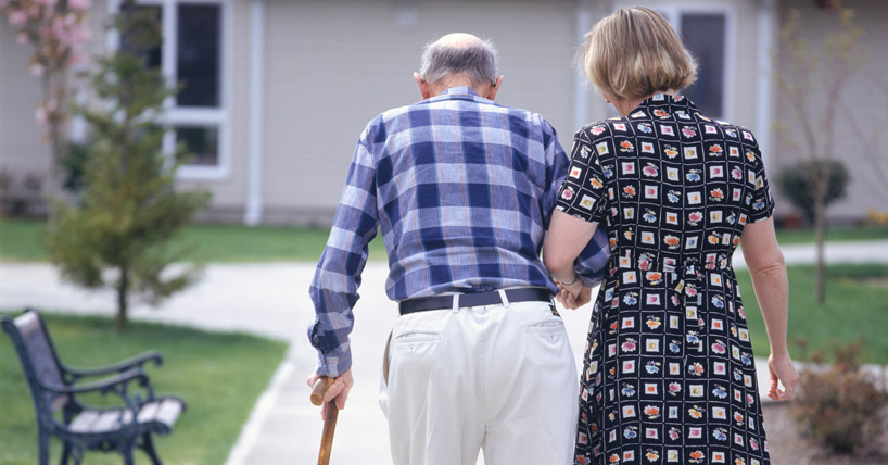 Woman helping senior man walk