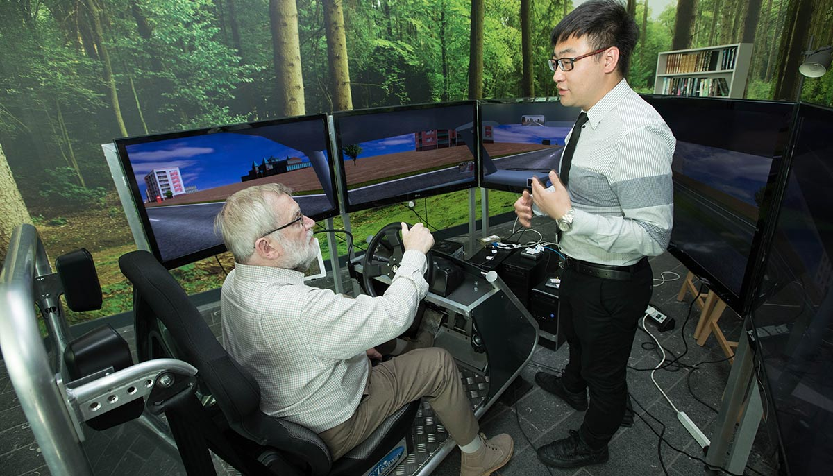 VOICE member Ian Fairclough on the Driving Simulator with lead researcher Dr Shuo Li