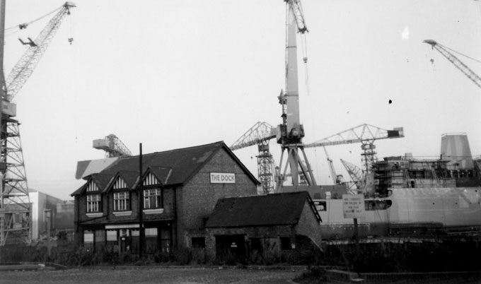 B&W photo of the Dock pub in Wallsend, Tyne and Wear, taken in the late 1980s. A ship and several of the iconic Swan Hunter shipyard cranes tower above the pub.