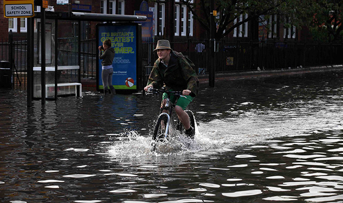 man on a bike cycling through a flood