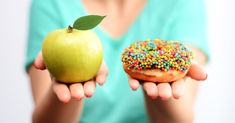 Image of woman holding an apple and a doughnut