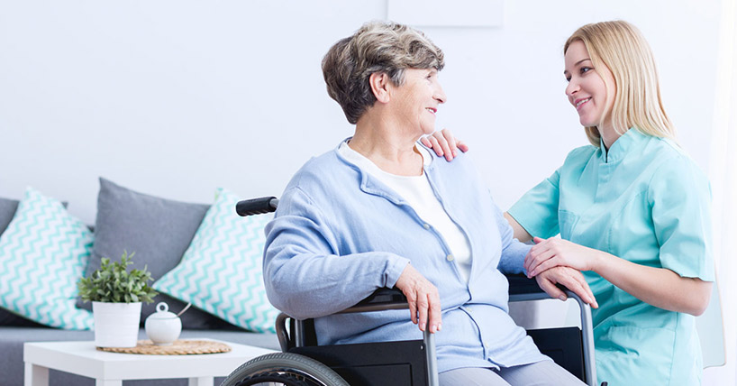 Nurse and elderly patient in a wheelchair.
