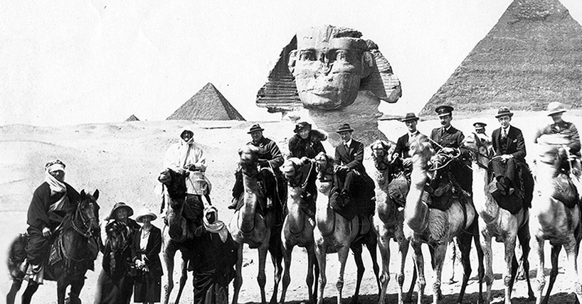 Black and white photo showing men and women on horseback near the Pyramids in Egypt
