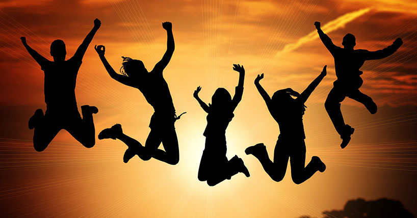 Children jumping in the air in front of sunrise.