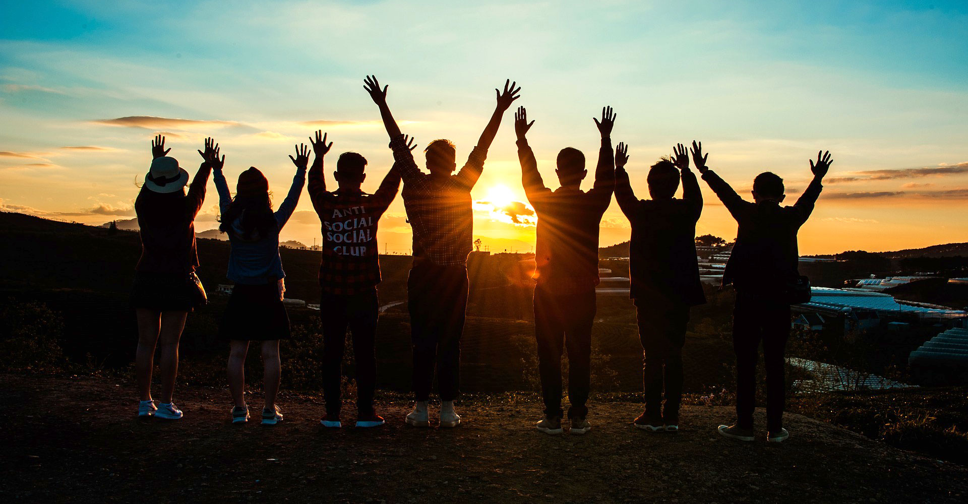 Emerging Minds: Teenagers with their hands in the air, at sunset.
