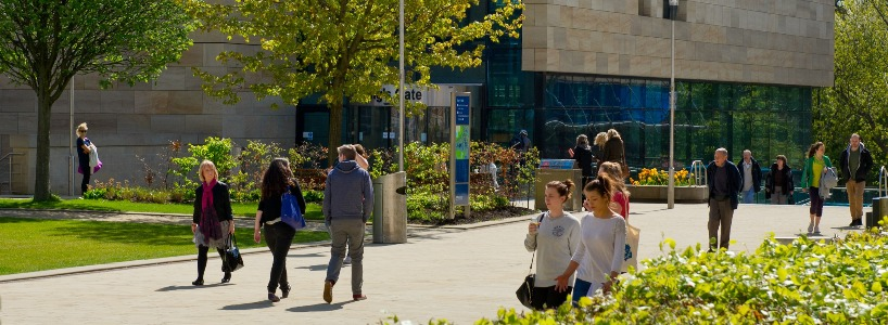 Students strolling on King's Walk in the sunshine.