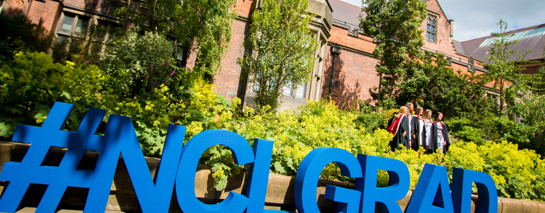 Giant foam letters spell out '#nclgrad' outside of the Percy Building.