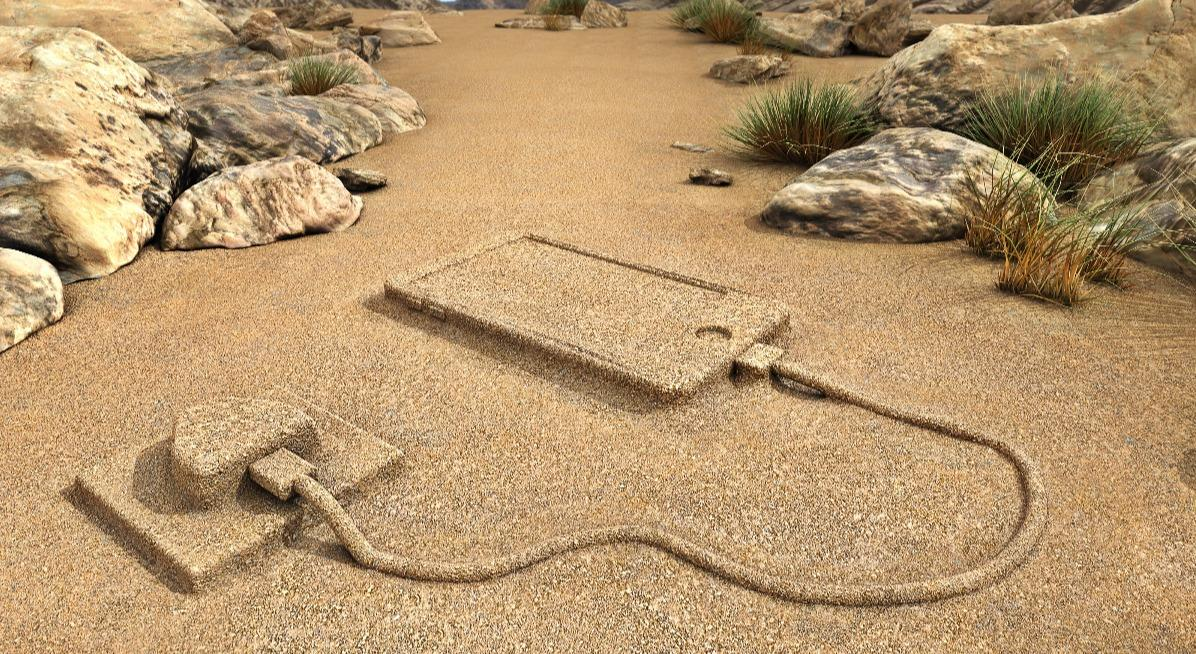 An abstract image of a smartphone plugged into the desert sand.