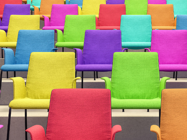 Empty, multicoloured chairs in a lecture theatre.