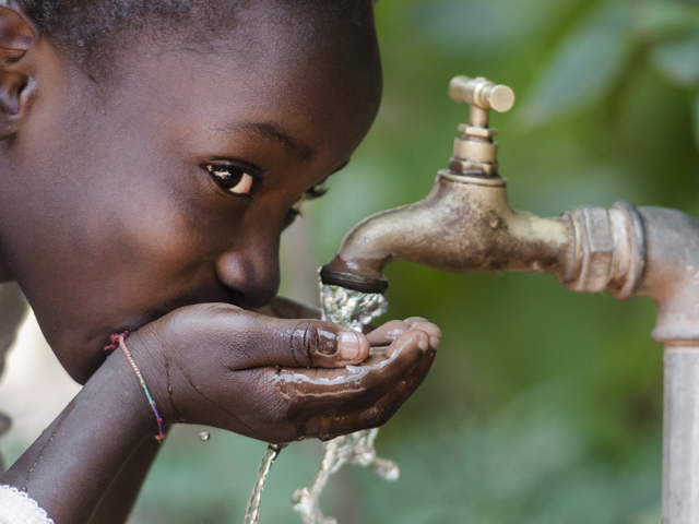 A child drinking water from a tap.