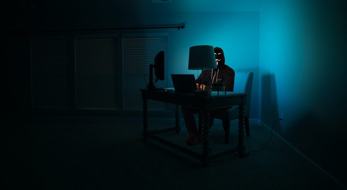 A masked person sitting in a dark room in front of a computer screen.