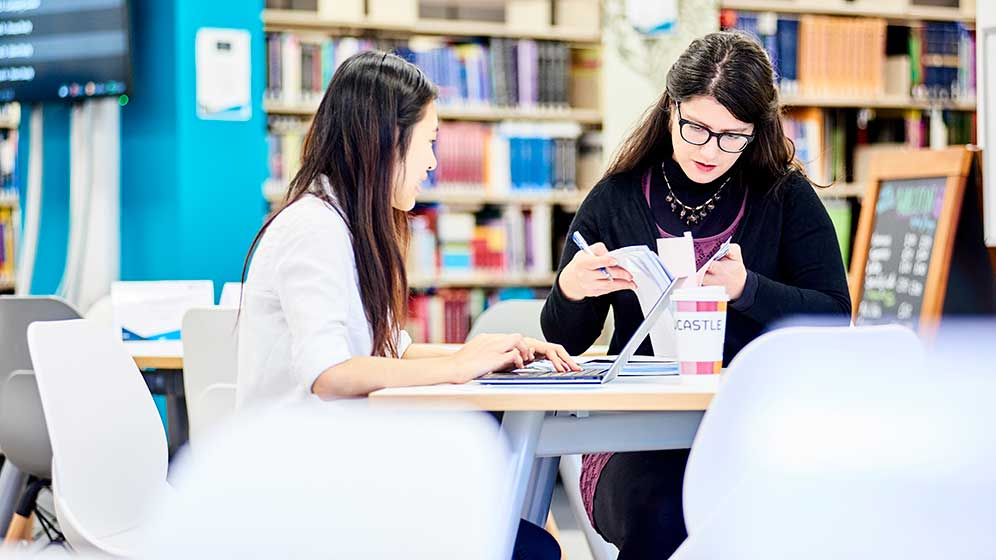 Two students working together in the dental school library.