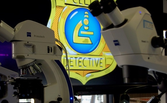 Two microscopes with the cell detectives emblem in the background