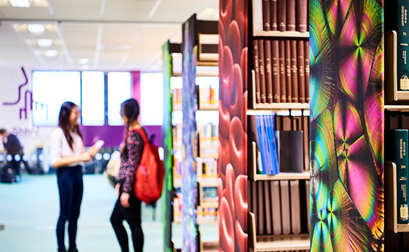 Students and bookshelves in the Walton Library