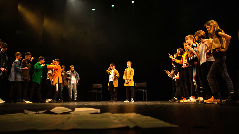 School children performing in a theatre