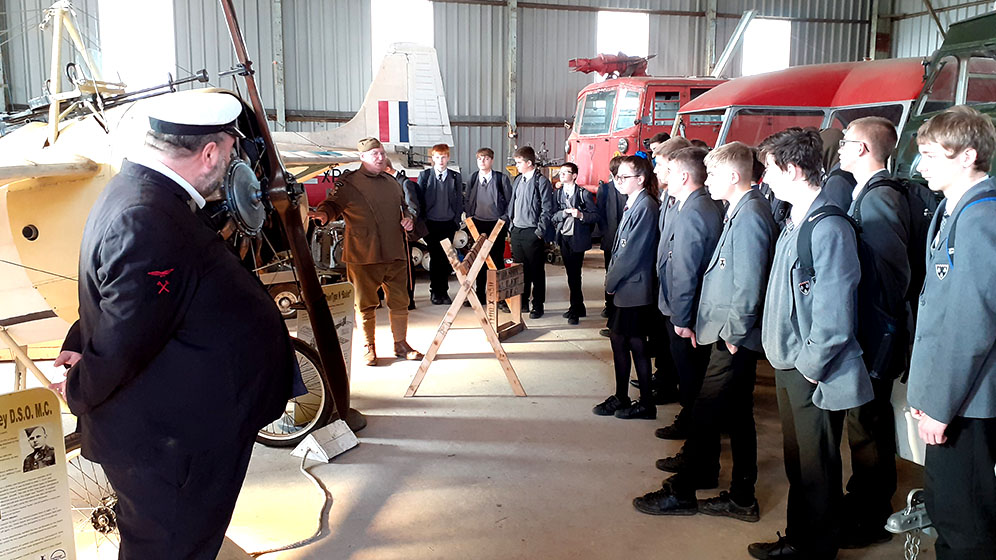 Students listening to a talk in a transport museum