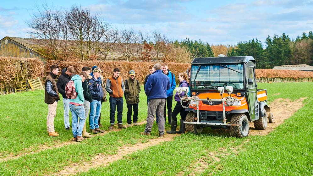Students crowd round a farm vehicle at the University's Cockle Park Farm