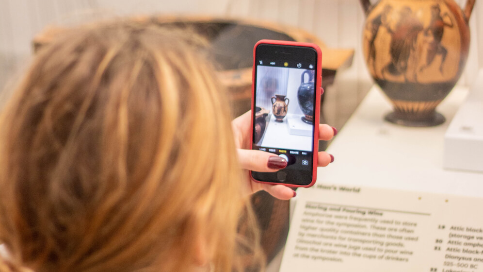 A student photographs an artefact in the Great North Museum