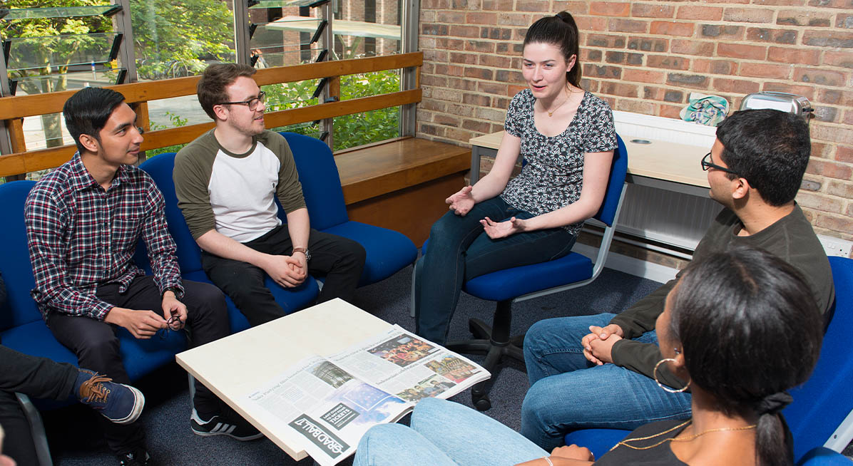 Students sit around a table chatting