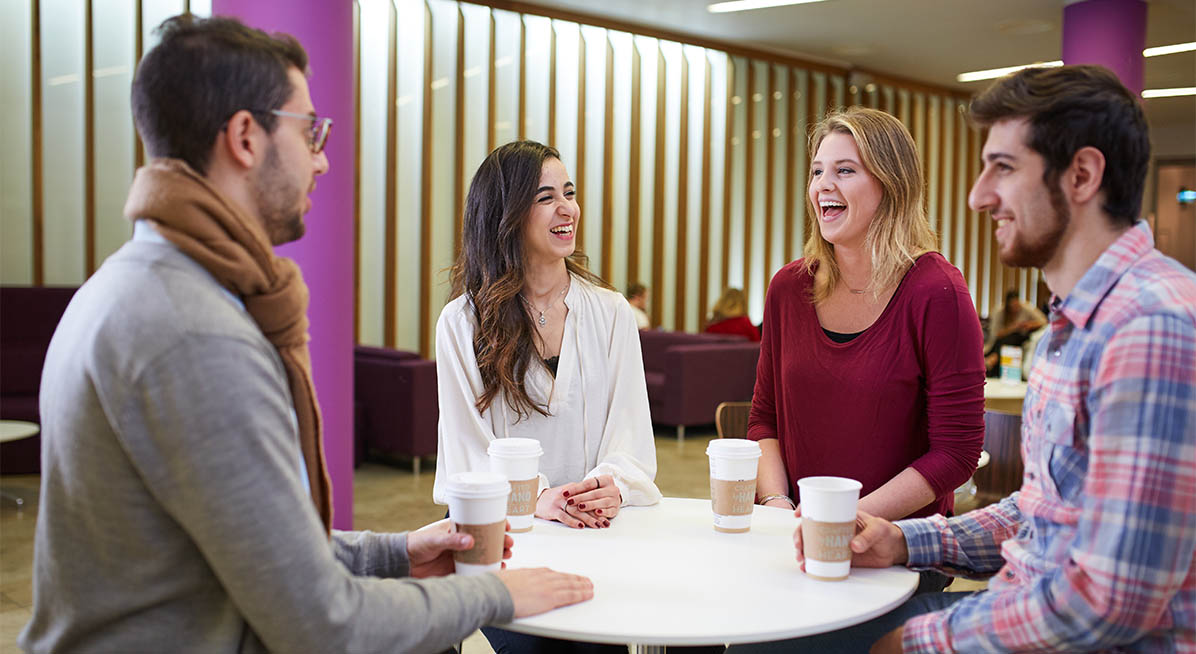 Students laugh while chatting in the Business School reception